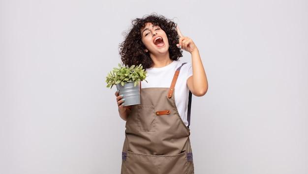 Молодая женщина-садовник чувствует себя счастливым и взволнованным гением после реализации идеи
