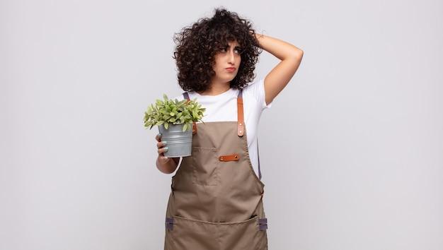 젊은 여성 정원사는 의아해하고 혼란스러워하고 머리를 긁고 옆을 바라보고 있습니다.