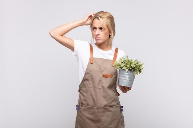 若い女性の庭師は戸惑い、混乱し、頭を掻き、横を向いていると感じています