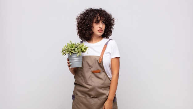 Young woman gardener feeling sad, upset or angry and looking to the side with a negative attitude, frowning in disagreement