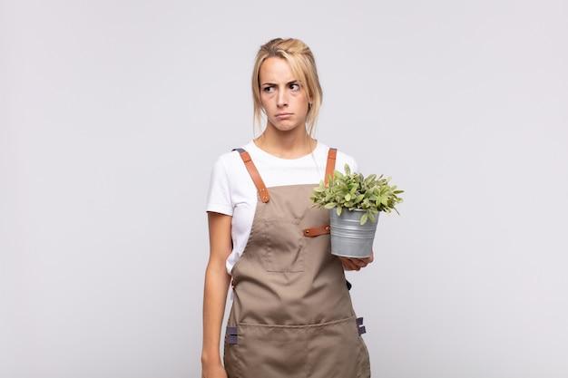 若い女性の庭師は、悲しみ、動揺、または怒りを感じ、否定的な態度で横を向いて、意見の相違に眉をひそめています