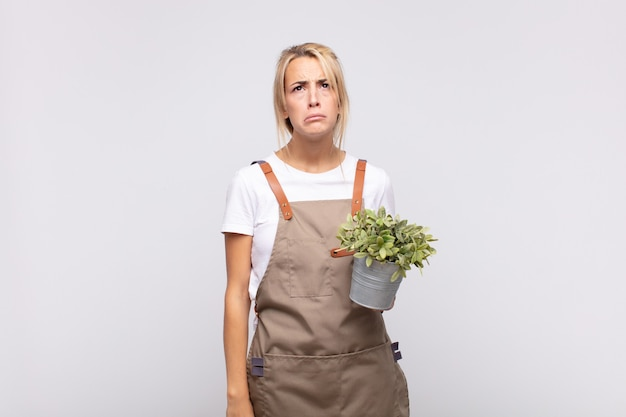 Young woman gardener feeling sad and whiney with an unhappy look, crying with a negative and frustrated attitude