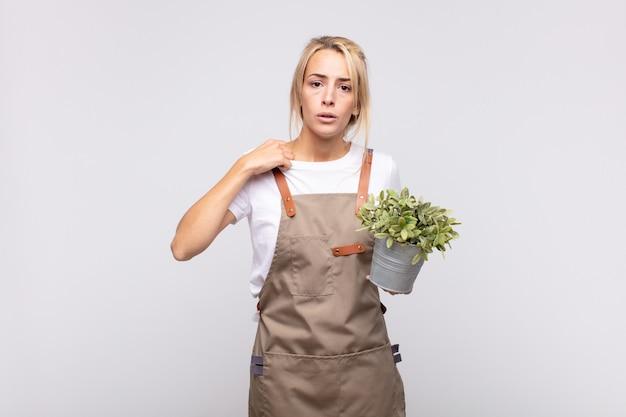 젊은 여성 정원사는 스트레스를 받고, 불안하고, 피곤하고, 좌절하고, 셔츠 목을 당기고, 문제에 대해 좌절감을 느끼고 있습니다.