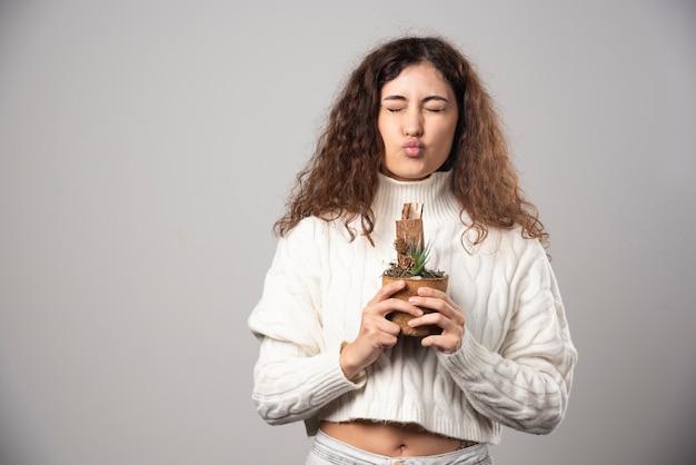 灰色の壁に植物を保持している若い女性の庭師。高品質の写真