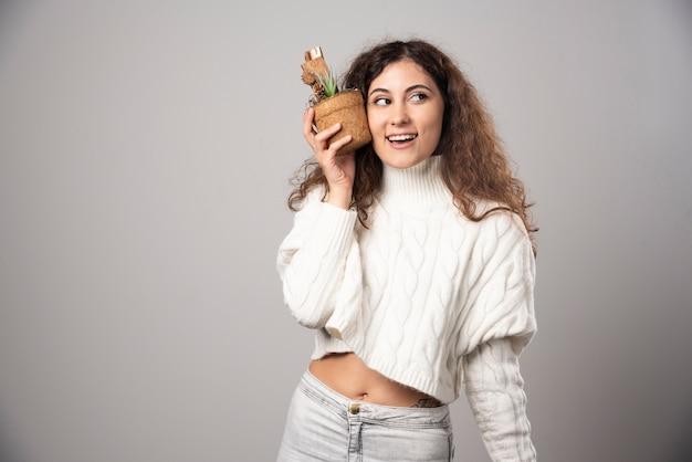 Giardiniere della giovane donna che tiene una pianta su un muro grigio. foto di alta qualità