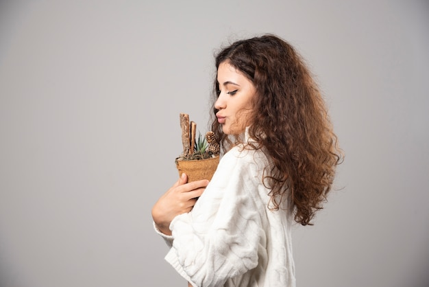 Young woman gardener holding a plant on a gray wall. high quality photo