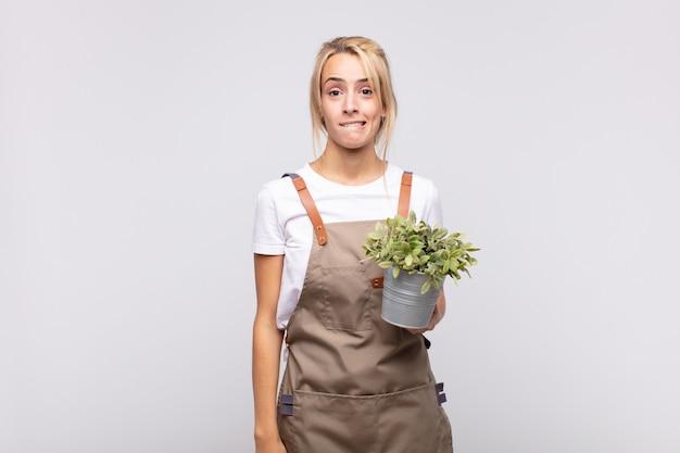 의아해하고 혼란스러워 보이는 젊은 여성 정원사, 문제에 대한 답을 모르는 긴장된 몸짓으로 입술을 물고