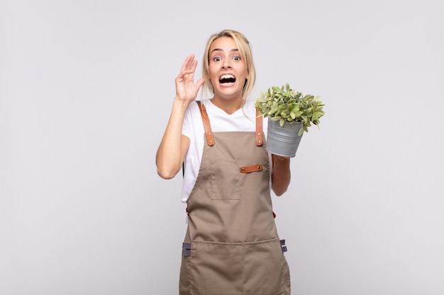 Young woman gardener screaming with hands up in the air, feeling furious, frustrated, stressed and upset