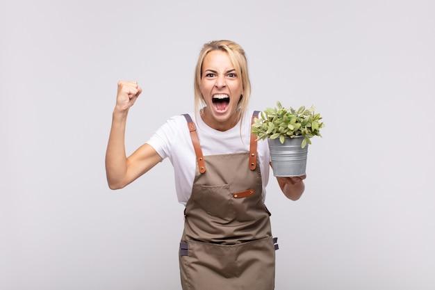 화가 난 표정으로 또는 주먹으로 공격적으로 외치는 젊은 여성 정원사는 성공을 축하합니다.