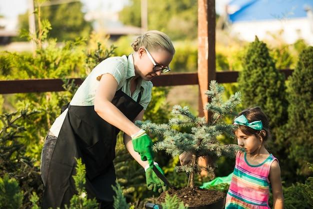 若い女性の庭師は、肥沃な土壌に植物を移植する女の子を示しています