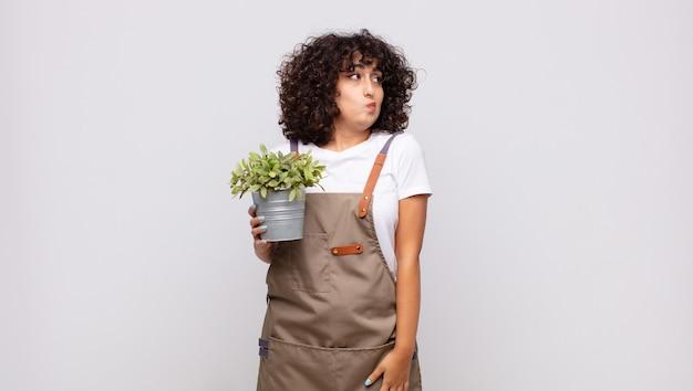 젊은 여성 정원사는 어깨를 으쓱하고, 혼란스럽고 불확실한 느낌, 팔을 교차하고 당황한 표정으로 의심
