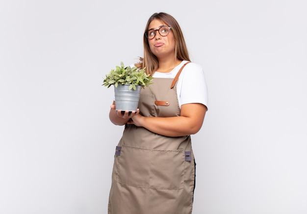 若い女性の庭師は肩をすくめ、混乱して不確かに感じ、腕を組んで困惑した表情で疑っています