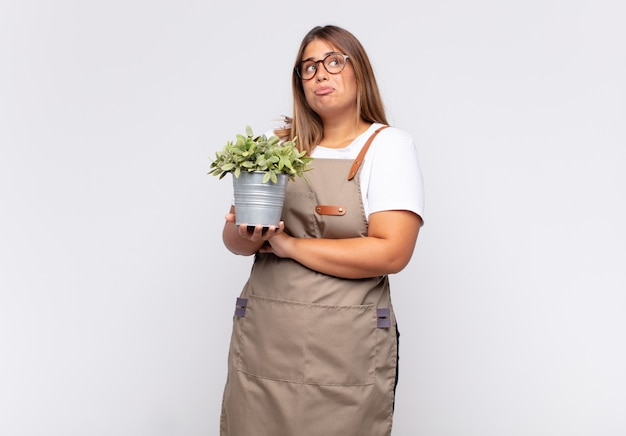 Young woman gardener shrugging, feeling confused and uncertain, doubting with arms crossed and puzzled look