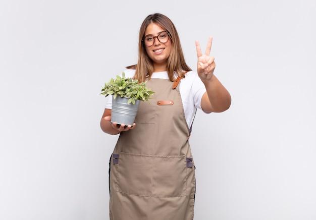 젊은 여자 정원사 웃고 행복하고 평온하고 긍정적 인, 승리 또는 평화를 한 손으로 몸짓으로보고