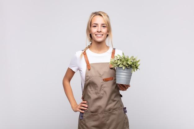 엉덩이에 손을 대고 행복하게 웃고 있는 젊은 여성 정원사, 자신감 있고 긍정적이고 자랑스럽고 친절한 태도
