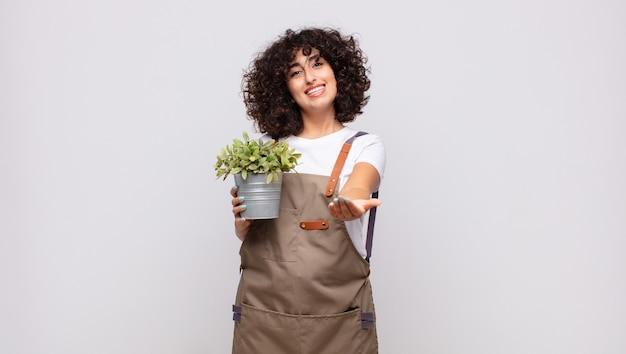 젊은 여성 정원사는 친절하고 자신감 있고 긍정적인 표정으로 행복하게 웃고 물건이나 개념을 제공하고 보여줍니다.