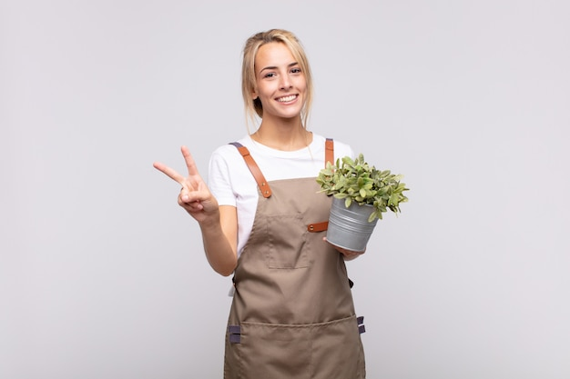 Young woman gardener smiling and looking friendly, showing number two or second with hand forward, counting down