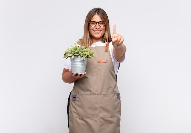 자랑스럽게 웃고 자신있게 넘버원 포즈를 취하는 젊은 여성 정원사