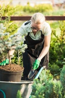 Молодая женщина-садовник пересаживает растение в плодородную почву