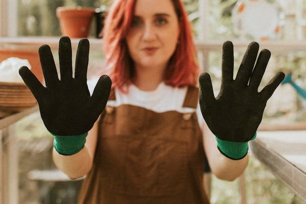 작은 유기 농장에서 검은 장갑과 젊은 여자 정원사