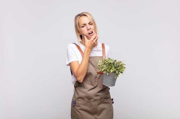 입과 눈을 크게 뜨고 턱에 손을 대고 불쾌한 충격을 받은 젊은 여성 정원사