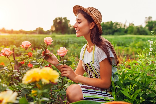 Young woman gathering flowers in garden. middle-aged woman smelling and admiring roses.