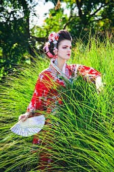 Young woman in geisha costume with a fan in green grass