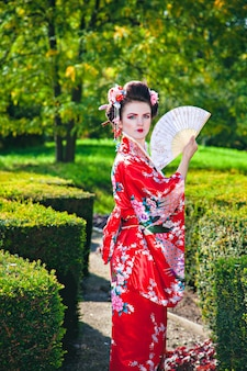 Young woman in geisha costume with fancy makeup in garden with a fan