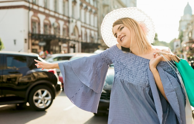 Young woman gestures to catch a car and talking on the phone on the roadway in the city. hitchhiking concept
