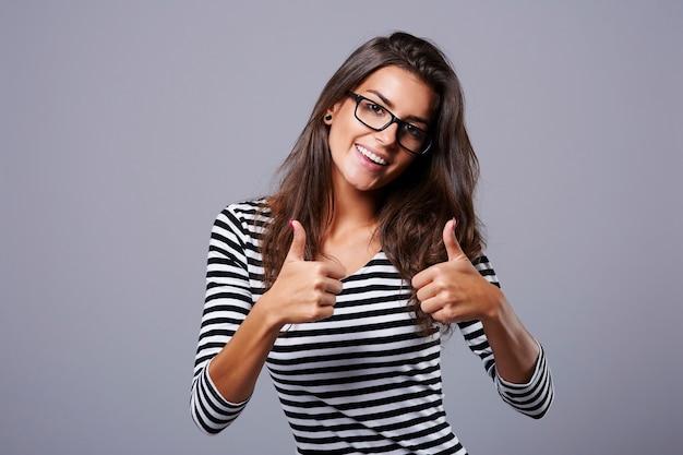 Giovane donna che gesturing un segno giusto