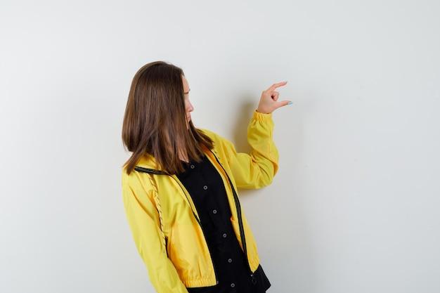 Giovane donna che gesticola di piccola taglia con le dita