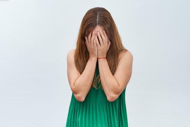 白い背景に悲しいことを身振りで示す若い女性。