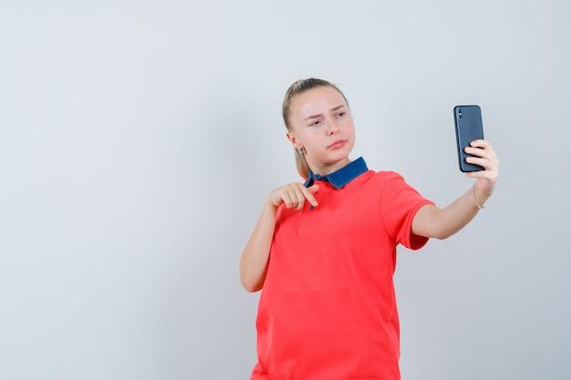 Giovane donna gesticolando tenendo selfie in t-shirt e guardando fiducioso