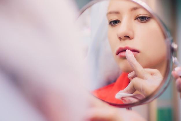 若い女性は美容サロンで彼女の唇に注射を取得します。美容注射-美容師のオフィスで横になっている女性。ヒアルロン酸で唇を整え、輪郭を整え、活力を取り戻します