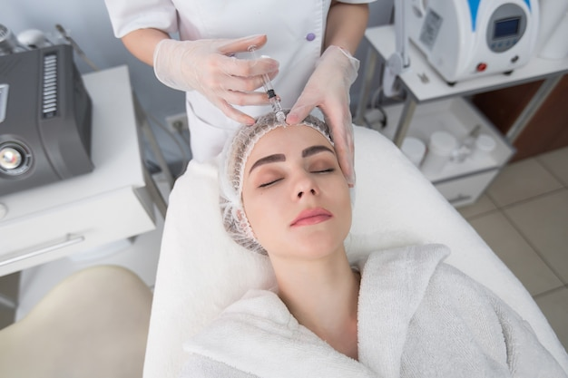 Young woman gets beauty facial injections in the cosmetology salon