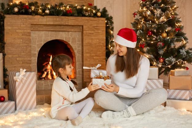 若い女性は2つのおさげの彼女のかわいい小さな娘からクリスマスプレゼントを受け取ります
