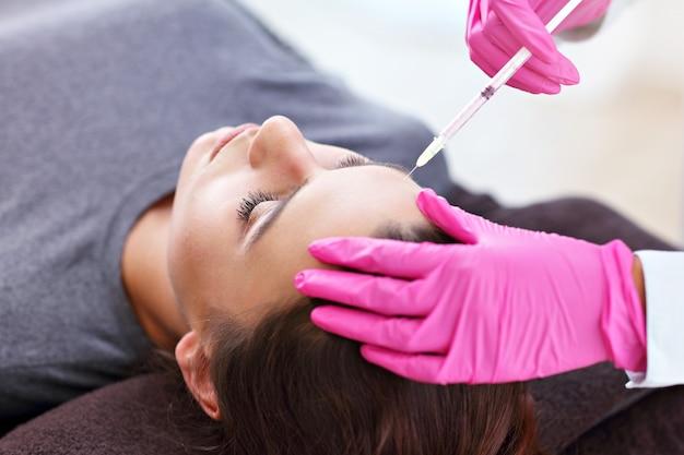若い女性が美容院で化粧顔注射を受ける