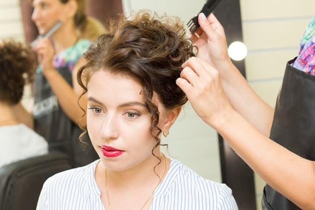 若い女性は美容院で髪を整えます