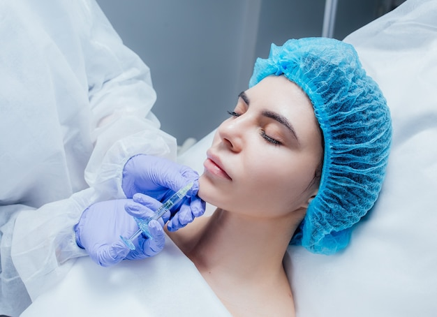 Young woman gets injection of botox in her lips. woman in beauty salon