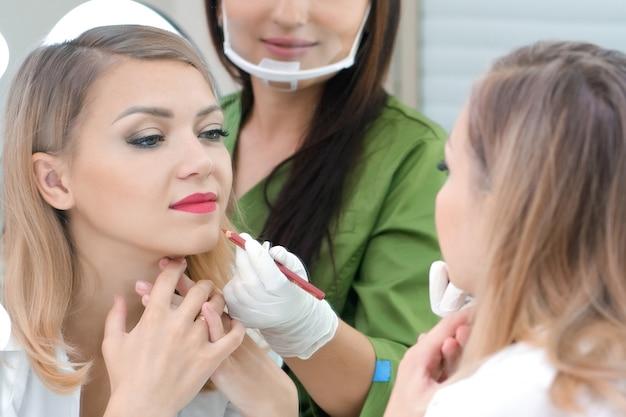 Молодая женщина получает макияж. татуировка губ в салоне красоты.