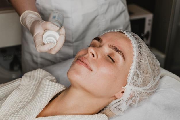 스파에서 얼굴 피부 치료를 받고 젊은 여자