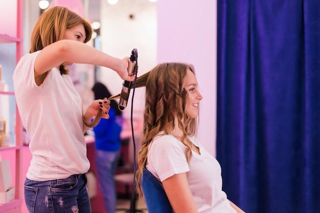 살롱에서 머리를 받고 젊은 여자. 헤어 컬링 아이언을 사용하여 스트레이트 헤어를 곱슬 머리로 바꾸는 헤어 스타일리스트. 프리미엄 사진