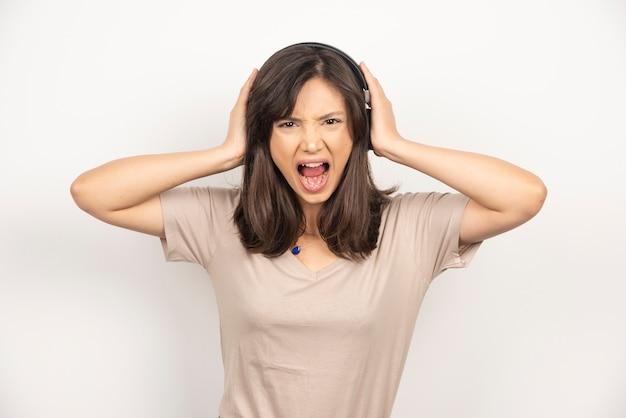 若い女性は白い背景に腹を立てています。