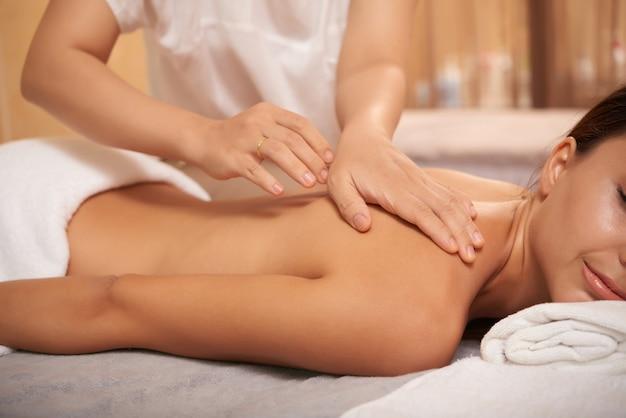 Giovane donna che ottiene indietro massaggio nel salone della stazione termale