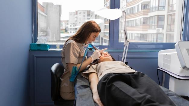 Giovane donna che ottiene un trattamento di bellezza per le sopracciglia