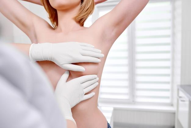 病院で乳房の検査を受けている若い女性