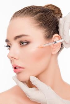 Молодая женщина получает косметическую инъекцию с помощью шприца
