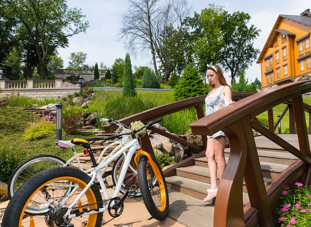 美しい高級公園で自転車に橋を降りる若い女性