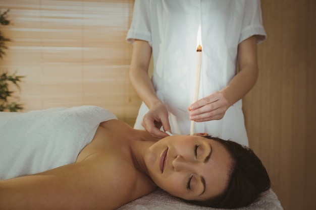 Young woman getting an ear candling treatment