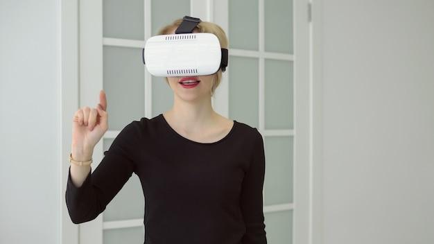 젊은 여성은 집에서 가상 현실의 vr 헤드셋 안경을 사용하여 많은 몸짓을 하는 손을 사용하여 경험을 얻고 있습니다.